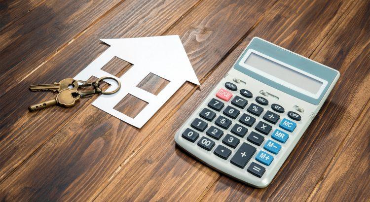 Kalkulačka a maketa na stole symbolizujúca hypotéku